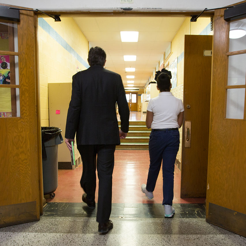 Adult and young student walking through hall of middle school