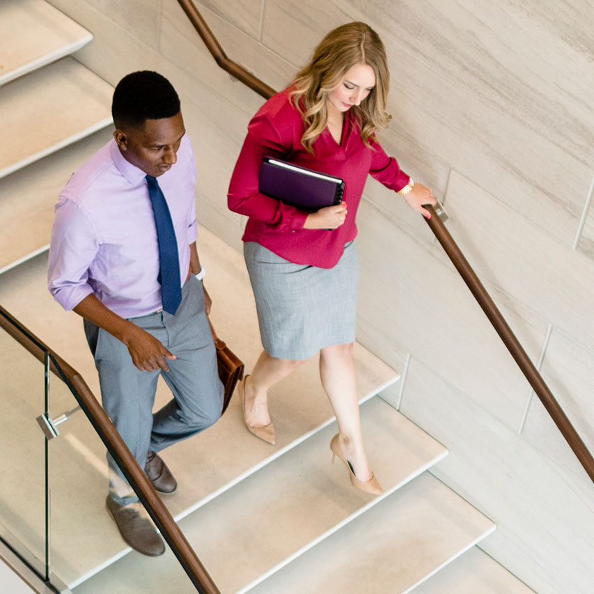 Two people walking down a staircase