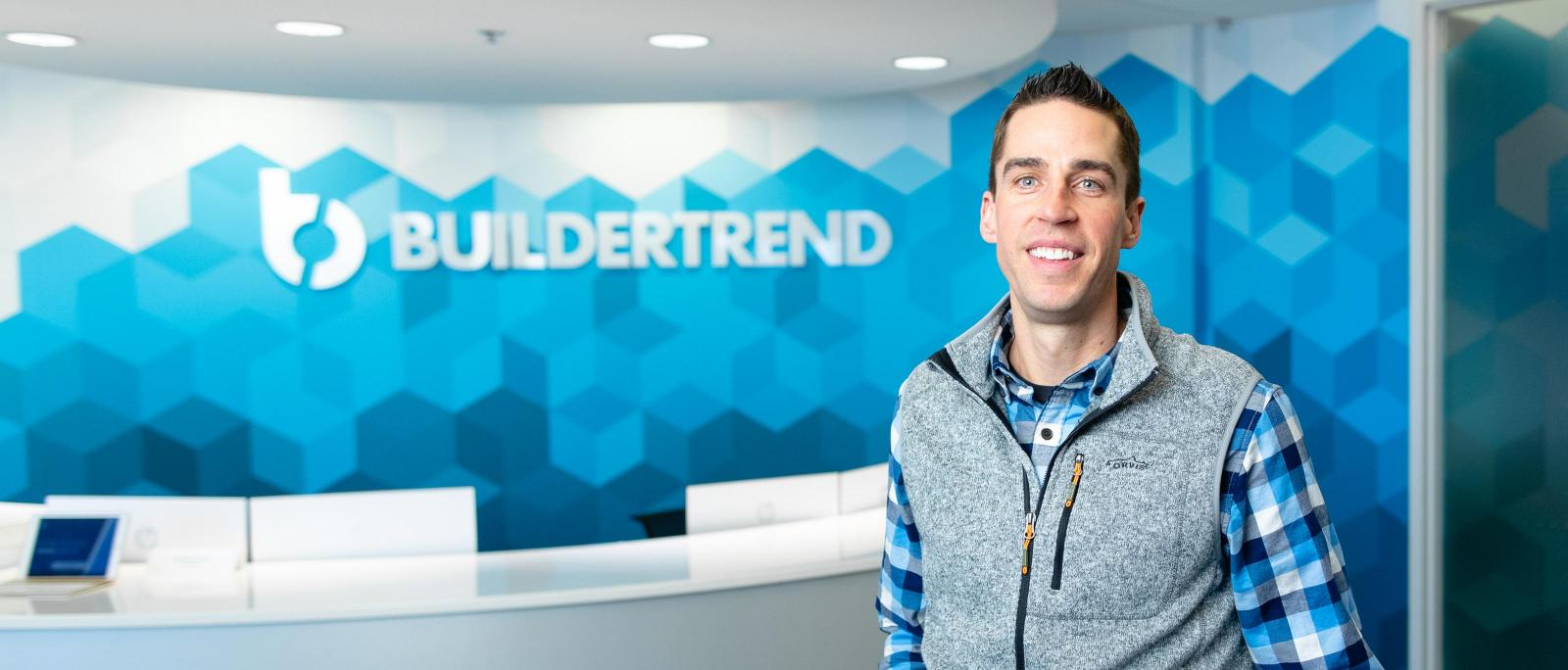 Luke Christiansen standing before Buildertrend sign