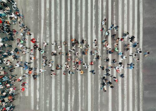 An aerial view of people walking across a street