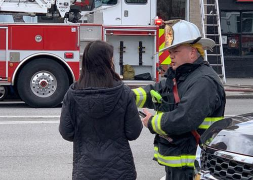 Brian-Schaeffer-Chief of Spokane Washington Fire Department, in uniform, talking with a woman before a fire truck