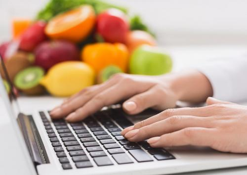 Woman's hands on a laptop with fruit in the background